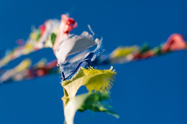 Bunte tibetisch-buddhistische gebetsfahnen, die im wind auf blau winken