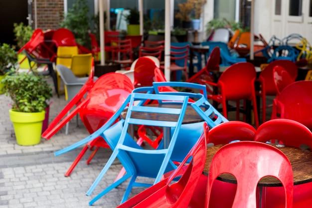 Bunte tische und stühle in einem café. gelbe, blaue, rote farben. europäisches restaurant in der stadt