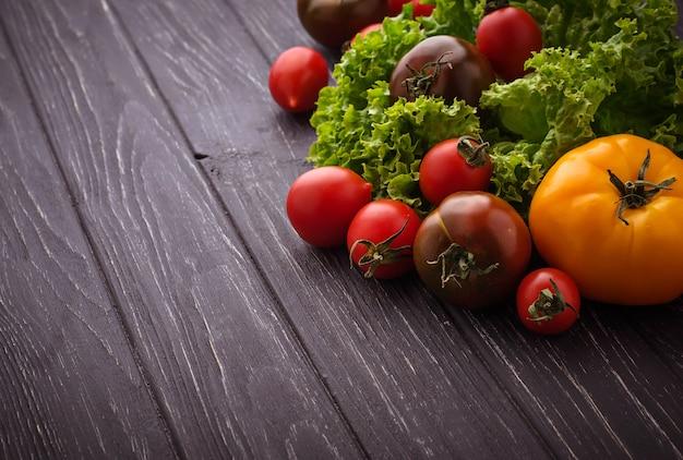 Bunte tomaten auf schwarzem hintergrund