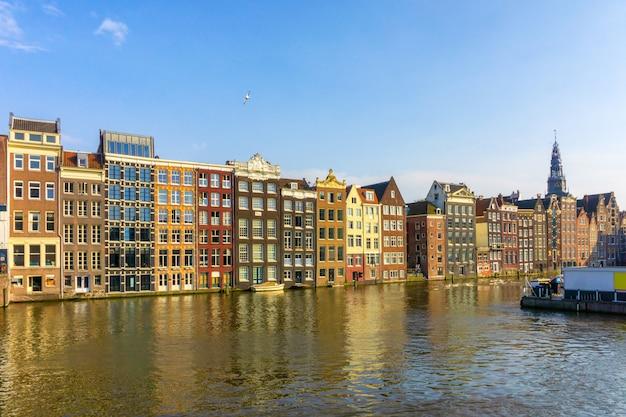 Bunte traditionelle altbauten am sonnenscheintag in amsterdam, die niederlande
