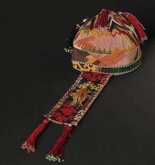 Bunte traditionelle asiatische schädelkappe mit zöpfen auf dunklem hintergrund