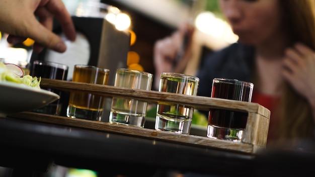 Bunte transparente cocktails, eine reihe von shots in einer reihe, sechs portionen auf einem holzständer, substrat. getränk für das menü restaurant, bar, café