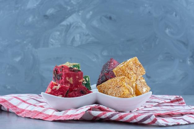 Bunte türkische köstlichkeiten auf einer schüssel, auf dem geschirrtuch, auf marmortisch.