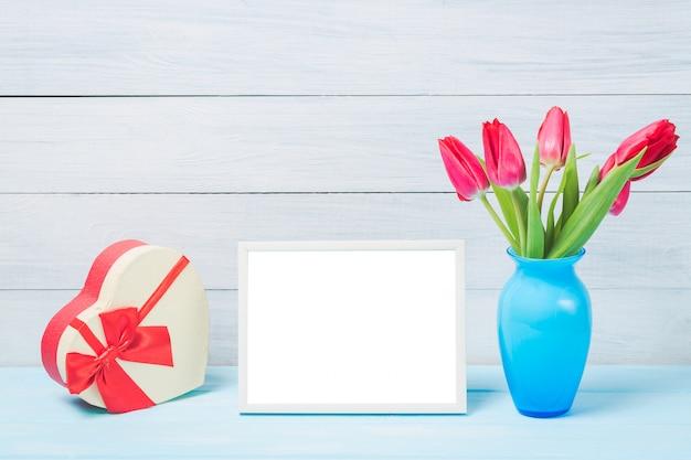 Bunte tulpe des roten frühlinges blüht im netten blauen vase und im leeren fotorahmen mit dekorativer herzgeschenkbox auf hellem hölzernem hintergrund