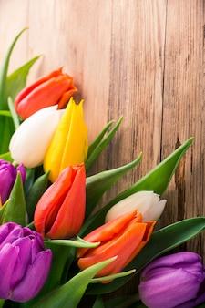 Bunte tulpen auf altem hölzernem hintergrund