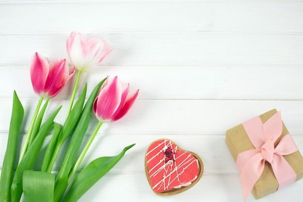 Bunte tulpen, herzplätzchen und geschenkbox auf weißem holzschreibtisch. draufsicht mit kopierraum.