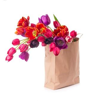Bunte tulpen in einer papiertüte auf einem weißen hintergrund.