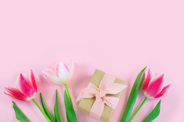 Bunte tulpen und geschenkbox auf rosa schreibtisch. draufsicht mit kopierraum.