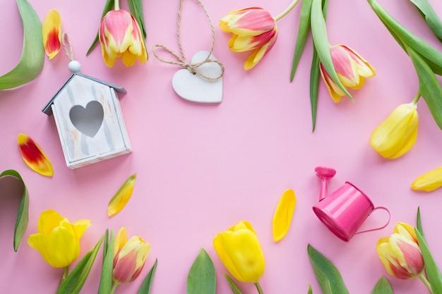 Bunte tulpen, vogelhaus, gießkanne holz auf rosa hintergrund gehört. konzept der oster- oder frühlingszeit