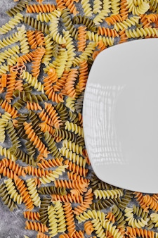 Bunte ungekochte fusilli neben weißem teller auf weiß.