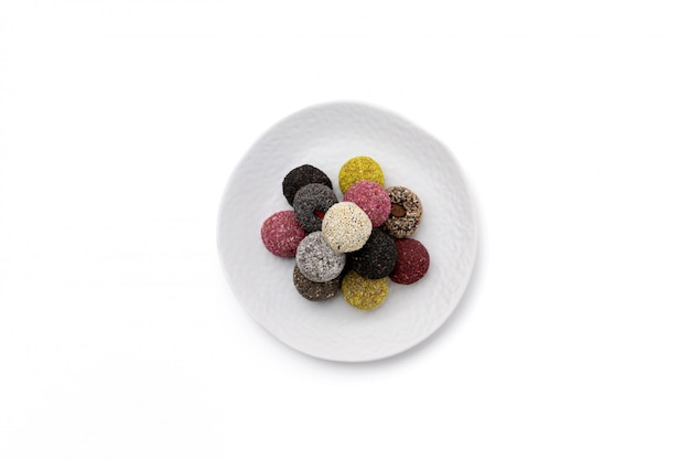 Bunte vegane bonbons energiekugeln auf platte lokalisiertes weiß
