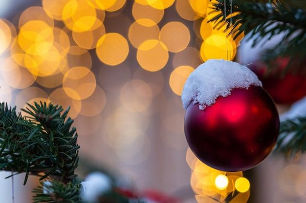 Bunte verzierungen auf schneebedeckten weihnachtsbaumzweigen. defokussierter hintergrund mit weihnachtslichtern.