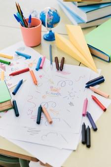 Bunte wachsmalstifte zerstreuten auf schreibtisch mit kinderzeichnungen