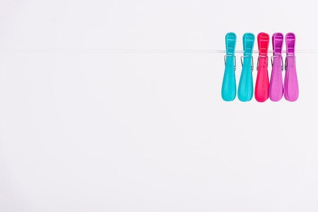 Bunte wäscheklammern, die an der weißen wäscheleine hängen