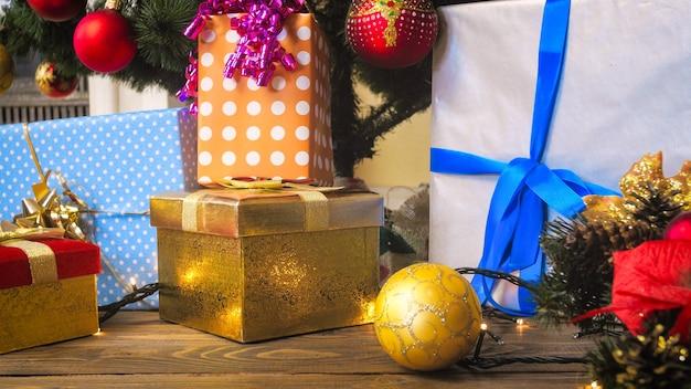 Bunte weihnachtsdekorationen, geschenke und kranz mit kerzen im wohnzimmer
