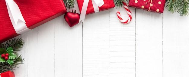 Bunte weihnachtsgeschenkboxen auf weißem hölzernem fahnenhintergrundgrenzdesign