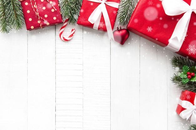 Bunte weihnachtsgeschenkboxen auf weißem hölzernem hintergrundgrenzdesign