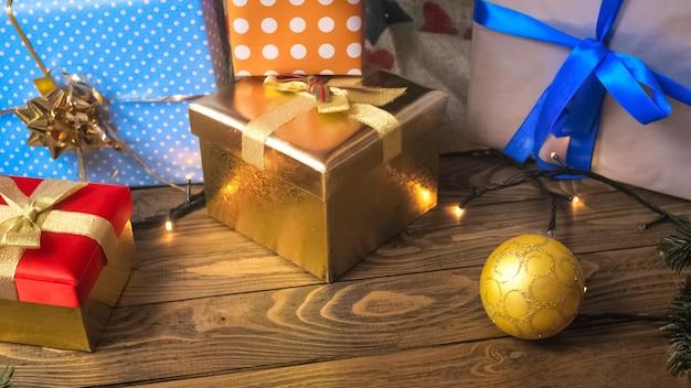 Bunte weihnachtsgeschenke und geschenk auf holzuntergrund. perfektes bild für feiertage und winterfeiern