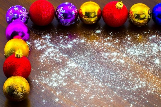 Bunte weihnachtskugeln des neuen jahres auf einem holztisch.