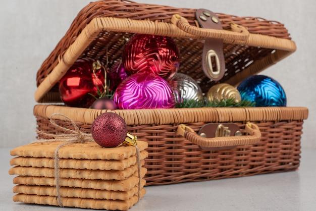 Bunte weihnachtskugeln im korb mit keksen im seil.