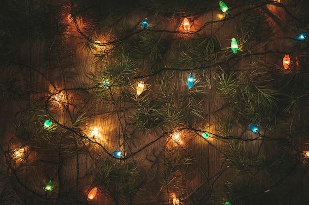 Bunte weihnachtslichter und die grünen zweige des weihnachtsbaums auf holztisch