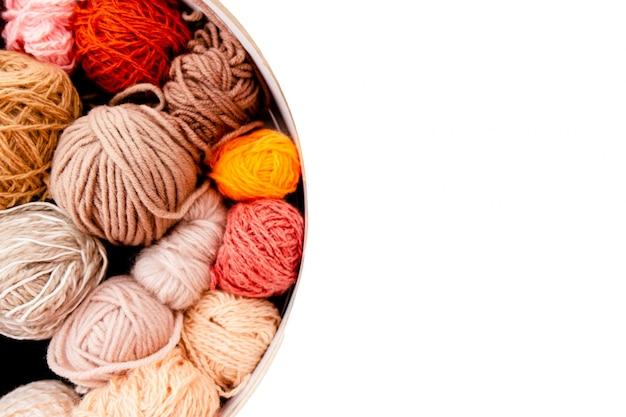Bunte wollknäuel mit stricknadeln auf weißem hintergrund, hobby und freizeitkonzept. garne zum stricken von copyspace