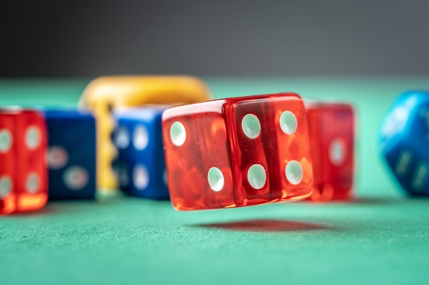 Bunte würfel auf dem grünen tisch. das konzept eines casinos und eine glückliche chance zu gewinnen