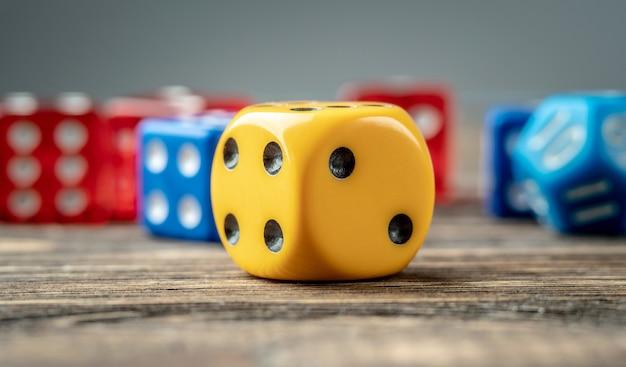 Bunte würfel auf dem holztisch. das konzept eines casinos und eine glückliche chance zu gewinnen