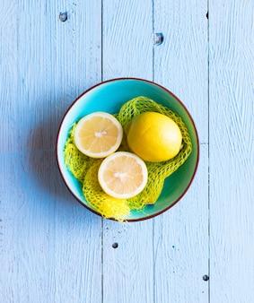 Bunte zitrone trägt über einer hellblauen gemalten hölzernen tabelle früchte