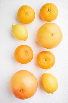 Bunte zitrusfrüchte, auf weißem steintischhintergrund, draufsicht flach