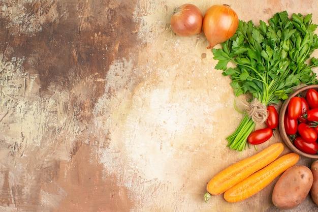 Bunte zutaten der draufsicht für die zubereitung von frischem salat auf einem hölzernen hintergrund mit platz für text
