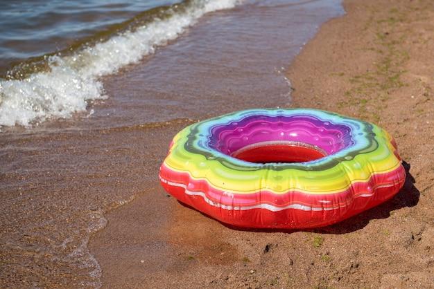 Bunter aufblasbarer smaragdkreis zum schwimmen am sandstrand
