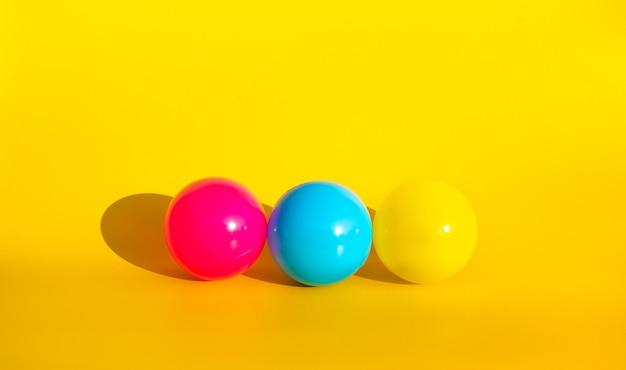 Bunter ballon mit schatten auf gelbem farbhintergrund. party- und feierkonzeptideen