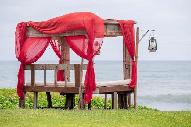 Bunter bogenpavillonpavillon, der vom holz und vom roten textil am tropischen strand in insel bali, indonesien gemacht wird