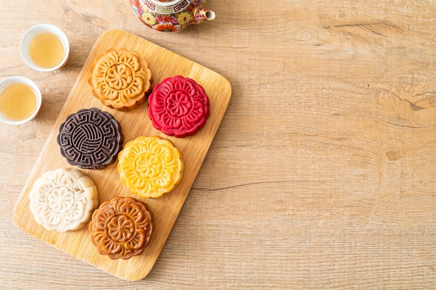 Bunter chinesischer mondkuchen mit gemischtem geschmack auf holzteller
