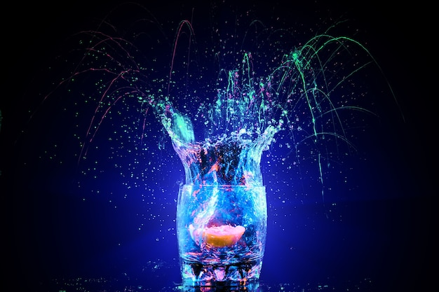 Bunter cocktail im glas mit spritzern und zitrone auf dunklem hintergrund. party club unterhaltung. gemischtes licht
