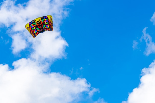 Bunter drachen im blauen himmel mit einer großen wolke