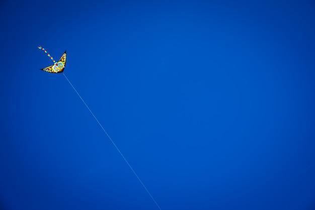 Bunter drachen mit fliegen des langen schwanzes im blauen himmel gegen die sonne, kopienraum.