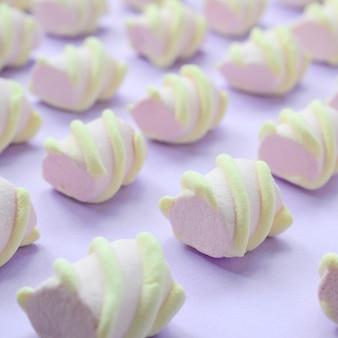 Bunter eibisch ausgebreitet auf violettem papierhintergrund. kreatives strukturiertes muster des pastells.