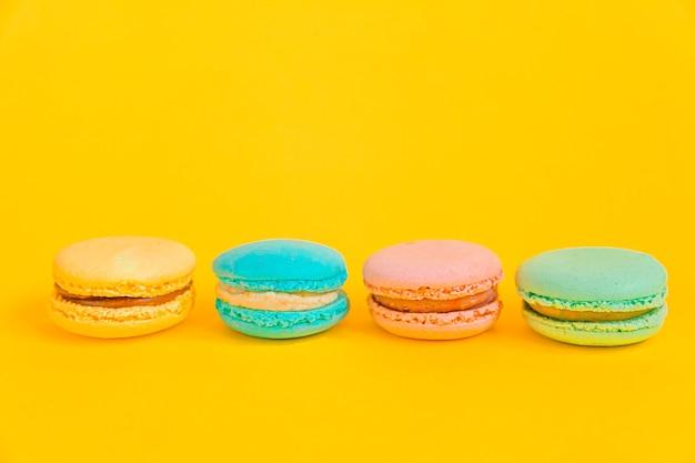Bunter einhornrosa blaues gelbes grünes macaron oder makronendessertkuchen der süßen mandel lokalisiert auf trendigem gelbem modernem modehintergrund.