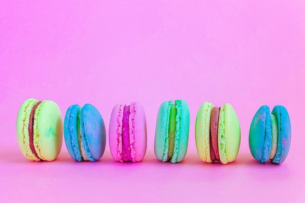 Bunter einhornrosa blaues gelbes grünes macaron oder makronendessertkuchen der süßen mandel lokalisiert auf trendigem rosa pastellhintergrund.
