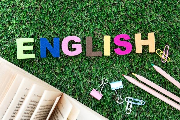 Bunter englischer wortwürfel auf yard des grünen grases, lernkonzept der englischen sprache