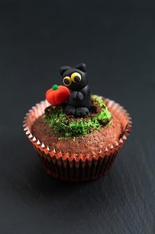 Bunter fantastischer schokoladenkuchenkleiner kuchen der halloween-feiertagsnahrung mit fondant der schwarzen katze und des kürbises verzieren