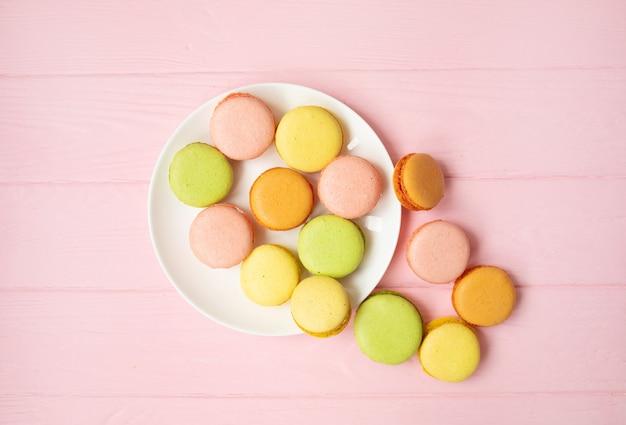 Bunter französischer oder italienischer macarons-stapel auf weißem teller, der auf rosa holztisch mit kopienraum für hintergrund gesetzt wird. dessert zum servieren mit nachmittagstee oder kaffeepause.