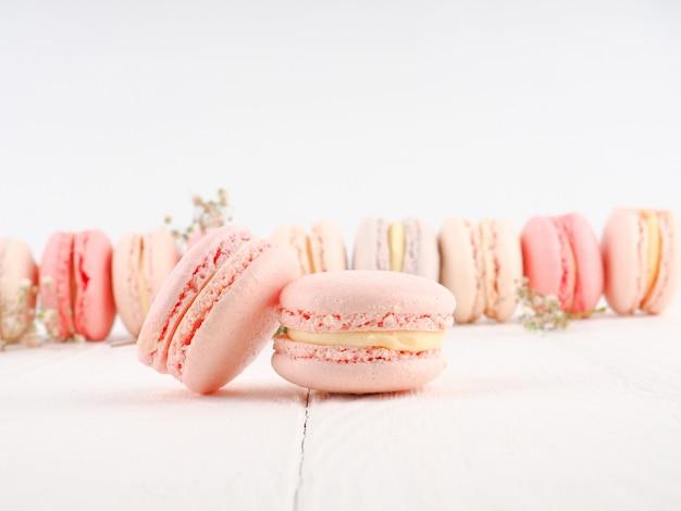 Bunter französischer oder italienischer macarons stapel auf weißer hölzerner tabelle. dessert mit nachmittagstee oder kaffeepause