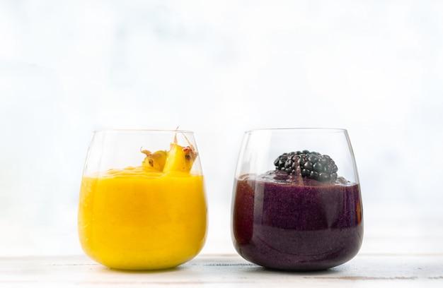 Bunter gelber und blauer smoothie in zwei gläsern