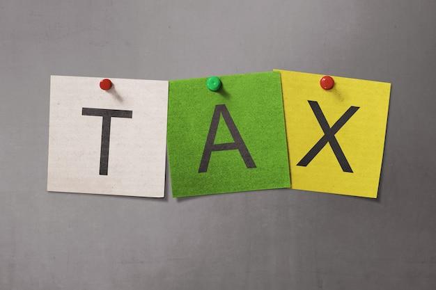 Bunter haftnotiz mit steuer-text mit roter reißzwecke