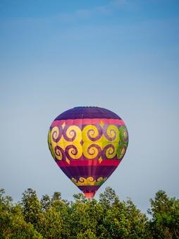 Bunter heißluftballon, der über blauen himmel fliegt