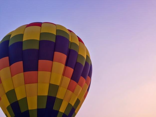 Bunter heißluftballon mit dämmerungshimmel.