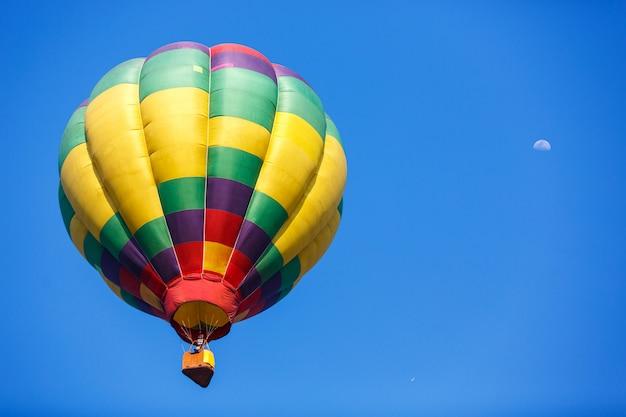 Bunter heißluftballon mit mond im blauen himmel